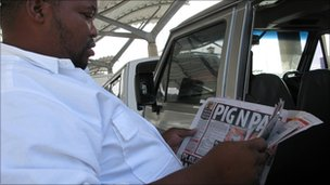 A minibus taxi reading a newspaper in Cape Town