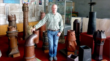 Lance Bates stands with some oh his collection of chimneys