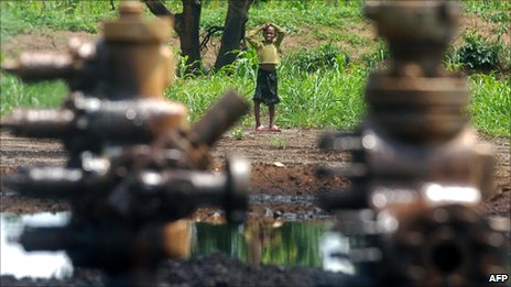A child looks towards an abandoned oil well head leaking crude oil in Kegbara Dere, Ogoni, Nigeria