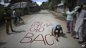 Protester writes anti-Indian graffiti on a road