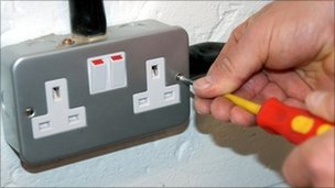 Electrician mending plug socket