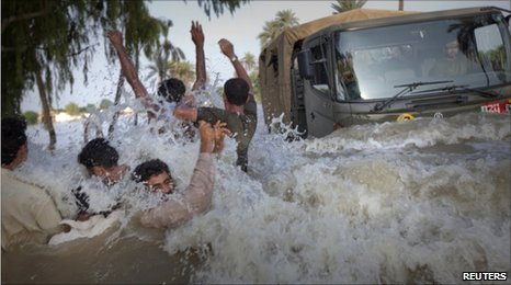Pakistan flood refugees dodge an army truck carrying relief supplies in Muzaffargarh, Punjab province