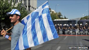 A trucker on strike holds a Greek flag in front of the Greek Parliament on July 30, 2010 during their protest march in Athens