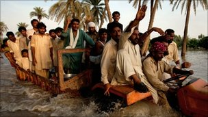 Villagers evacuated through floodwaters near Muzaffargarh, Punjab province, on 11 August 2010