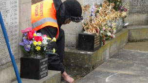 An offender straightens a paving slab