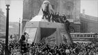 A few minutes after the Japanese surrender was announced, Piccadilly Circus was filled with a jubilant crowd, some of whom climbed on the plinth of the Statue of Eros.