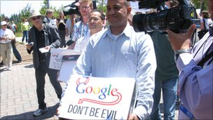 guy carrying a box of petitions with Google don't be evil sign