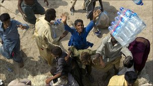 Flood victims grab aid being dropped from a Pakistan Army helicopter flying over Sindh province on 14 August 2010