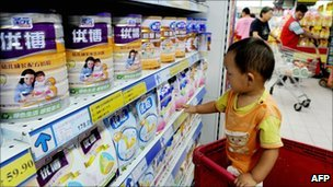 A Chinese baby looks at tins of Synutra milk powder at a supermarket in Beijing on 9 August 2010