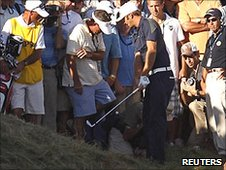 Dustin Johnson plays his shot among the spectators on the 18th
