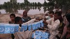 Displaced children make preparations to celebrate Independence Day in Qadirpur, Sindh province, on 13 August 2010
