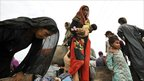Flood survivors sit on a tractor trolley in Karampur, Sindh province