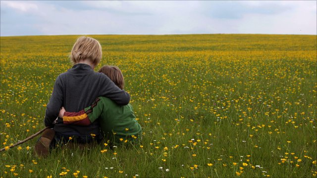 Two boys sitting in a field (generic image)