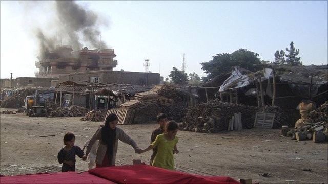 Afghan children walk along a Kunduz street as smoke rises from a suspected Taliban bomb attack, 2 July 2010