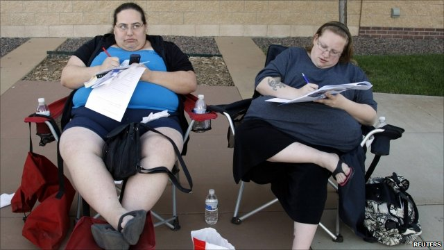 Two women fill out forms to apply for US TV show Biggest Loser