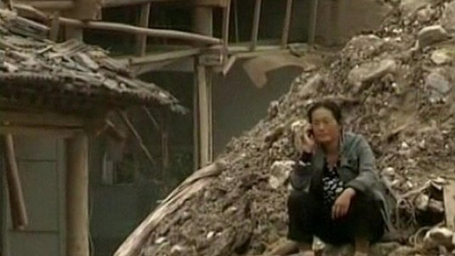 A woman sits on the rubble