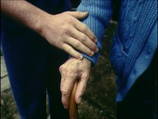 Man holds old woman's hand
