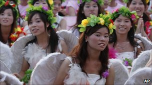Foxconn employees dressed as angels during a company rally in Shenzhen on 18 August 2010