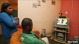 Kelly Regina dos Santos watches a presidential campaign programme with her husband Tone Ander Costa and their son Igor in the rural region of Estiva in the Brazilian state of Minas Gerais