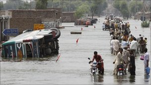 People on a flooded road at Muzaffargarh district, Punjab province, Pakistan, on 19 August 2010