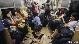Women board a women-only carriage of a commuter train in Jakarta