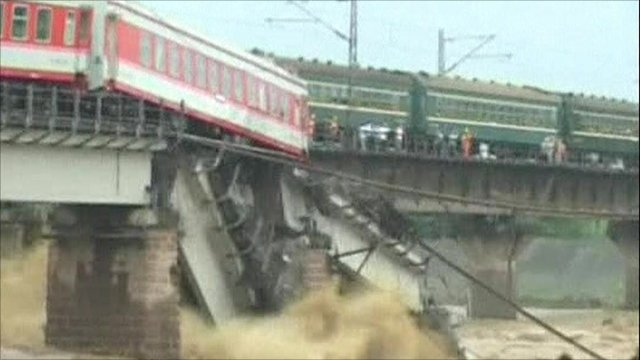 A train carriage dangling above the river