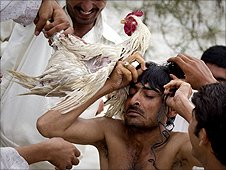 Residents help a man untie a chicken from his neck