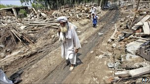 Flood survivors walk amid debris in Nowshera on 17 August 2010