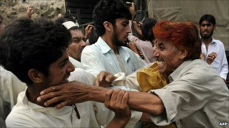 Pakistani flood victims fight for relief bags distributed by soldiers in Nowshera on 20 August 2010