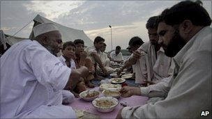 Pakistani flood survivors break their fast near Nowshera on 19 August 2010