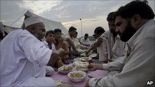 Pakistani flood survivors break their fast near Nowshera on 19 August 2010