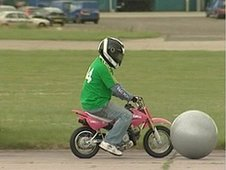 Mike Bushell on tiny motorbike during game of stuntbike football