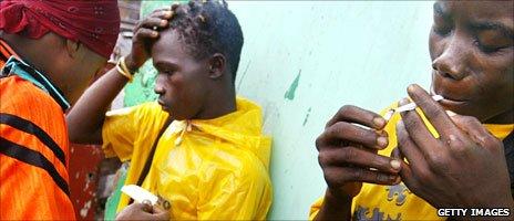 Teenagers loyal to the Liberian army smoke marijuana in Monrovia in July 2003