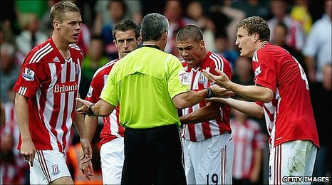 Stoke players remonstrate with referee Chris Foy