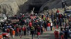 People gather outside the gold mine in Copiapo where 33 miners are trapped, 7 August 2010