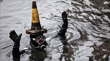 A scuba dive wears a traffic cone on his head