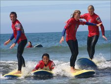 Achieng and Tom surfing in Plymouth