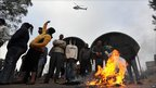 Striking civil servants protesting outside a hospital in Johannesburg stand by burning tyres and look up at police helicopter