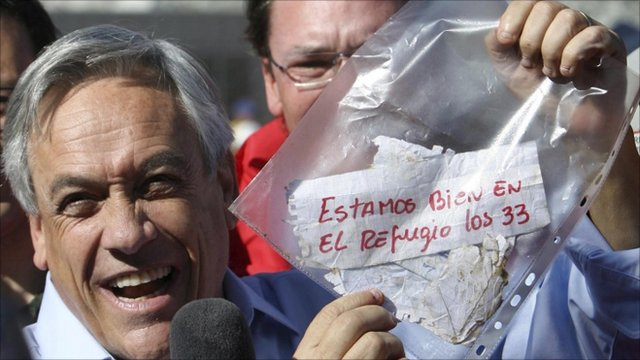 Chile's President Sebastian Pinera holds up a plastic bag containing a message, from miners trapped in a collapsed mine