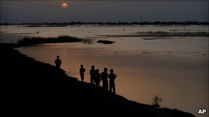 Children look at rising floodwaters near Shahdadkot in Sindh province at sunset (23 August 2010)