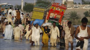 People walk through flood water in Baseera, Punjab province, Pakistan (23 August 2010)