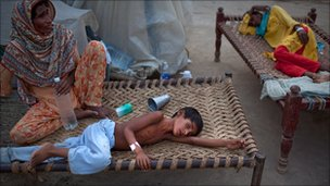 8 year old Yakub, suffering from Diarrhea lays on a bed next to his mother as he receives medical care at a makeshift hospital on August 22, 2010 in Muzaffargarh in Punjab