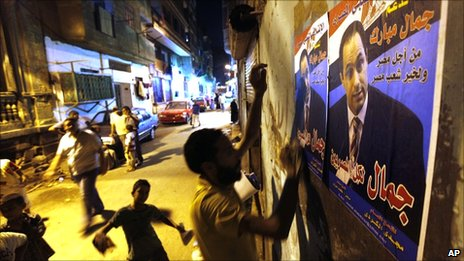"Egyptian activists of the Popular Coalition to Support Gamal Mubarak hang posters promoting the son of President Hosni Mubarak as the country's next leader, in Cairo, Egypt (21 August 2010). The Arabic reads ""Gamal for all Egyptians""."