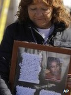 Liliana Ramirez holds a framed photo and letter from her husband