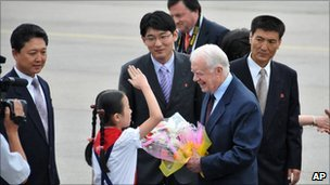 Jimmy Carter receives flowers from a North Korean child in Pyongyang on 25 August 2010