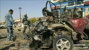 Iraqi security look at the remains of a car bomb in the city of Kirkuk