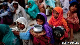 Pakistanis queue for food in a flood relief camp near Muzaffargarh in Punjab, Pakistan, on 25 August, 2010