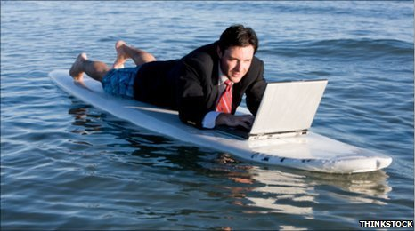 Man with a laptop on a surfboard