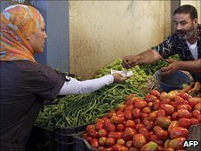 A woman buys vegetables in a market in Algiers