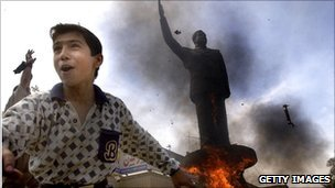 An Iraqi boy cheers as a statue of ousted Iraqi President Saddam Hussein